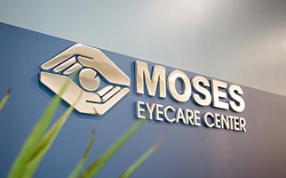 Moses Eyecare logo on a blue wall